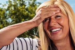 Reife Dame Holding Her Forehead Lizenzfreies Stockfoto