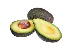 Reife dunkle Avocado und Avocadoschnitt zur Hälfte zwei mit einem braunen Stein stockbilder