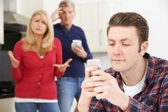 Reife Eltern frustriert mit dem erwachsenen Sohn, der zu Hause lebt stockbild