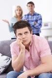 Reife Eltern frustriert mit dem erwachsenen Sohn, der zu Hause lebt stockbilder