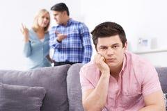 Reife Eltern frustriert mit dem erwachsenen Sohn, der zu Hause lebt lizenzfreie stockfotografie