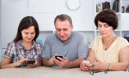 Reife Eltern mit der Tochter, die mit Telefonen sitzt Lizenzfreie Stockbilder