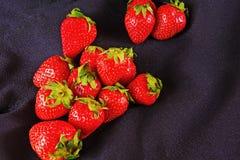 Reife Erdbeeren der Beeren auf einer schwarzen Oberfläche Stockfotografie