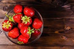 Reife Erdbeeren in der Glasschüssel auf Holztisch Beschneidungspfad eingeschlossen Lizenzfreie Stockbilder