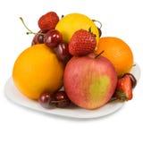 Reife Erdbeeren, Kirsche, Apfel, Orange und Zitrone auf der Platte Stockbild