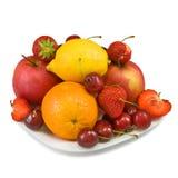 Reife Erdbeeren, Kirsche, Apfel, Orange und Zitrone auf der Platte Stockfotos
