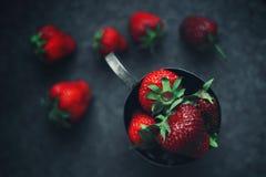 Reife Erdbeeren zerstreut um einen Eisenbecher Dunkles Foto lizenzfreie stockbilder