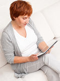 Reife erwachsene Frau mit Tabletten-PC Stockbild