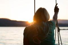 Reife Frau auf dem Schwingen, das Ozean gegenüberstellt Stockfotografie