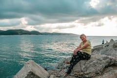 Reife Frau Beautifil, die auf den Steinen sitzt stockbilder