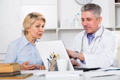 Reife Frau besucht Doktor Stockfotos