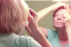 Reife Frau der Spiegelreflexion, die auf Make-up sich setzt Lizenzfreie Stockbilder