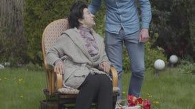 Reife Frau des Porträts, die auf dem Rasen im Schaukelstuhl genießt Sonne sitzt Erwachsener Enkel kommt und die Frau umarmend stock video footage