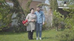 Reife Frau des Porträts mit dem Korb mit den Tulpen in den Händen sprechend mit ihrem Enkel auf dem Hinterhof Erwachsener Enkel u stock footage