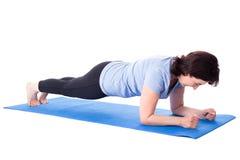 Reife Frau, die Übungen auf der Yogamatte lokalisiert auf Weiß tut Lizenzfreie Stockfotografie