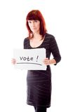 Reife Frau, die Abstimmungszeichen auf weißem Hintergrund zeigt Stockfotos