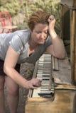 Reife Frau, die antikes hölzernes Klavier in der Wüsten-Einstellung spielt Stockfoto