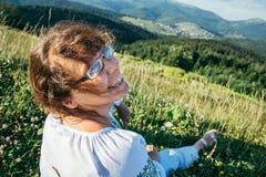 Reife Frau, die auf der Spitze des Hügels sitzt und die Ansicht enjoing Stockbild