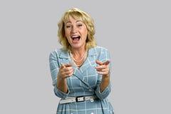 Reife Frau, die auf grauem Hintergrund lacht Lizenzfreie Stockfotos