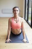 Reife Frau, die auf Mat In Gym trainiert Lizenzfreie Stockfotos
