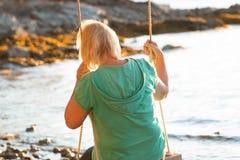 Reife Frau, die auf Schwingen am Strand stillsteht Lizenzfreie Stockbilder