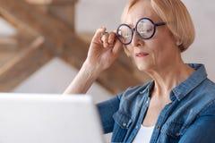 Reife Frau, die aufmerksam Laptop betrachtet Stockfoto