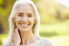 Reife Frau, die in Autumn Landscape sich entspannt lizenzfreie stockbilder