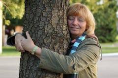 Reife Frau, die Baum umarmt Lizenzfreie Stockfotos