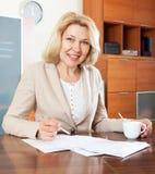 Reife Frau, die bei Tisch mit Dokumenten im Büroinnenraum arbeitet Lizenzfreies Stockfoto