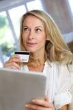 Reife Frau, die das on-line-Einkaufen mit Tablette tut Lizenzfreie Stockfotos