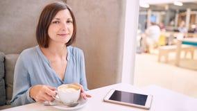 Reife Frau, die an der Kamera mit coffe und einer Tablette lächelt Lizenzfreie Stockfotos