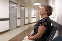 Reife Frau, die in Doktor ` s Büro wartet stockfotografie