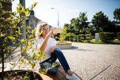 Reife Frau, die draußen, ein selfie anklickend sitzt Lizenzfreie Stockbilder