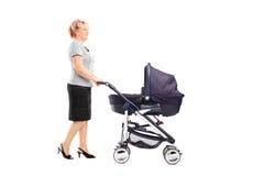 Reife Frau, die einen Kinderwagen drückt Lizenzfreies Stockfoto
