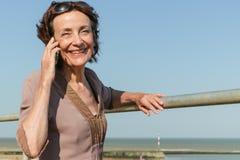 Reife Frau, die einen Telefonanruf macht Lizenzfreie Stockfotografie