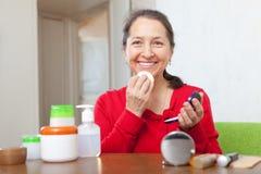 Reife Frau, die facepowder auf Gesicht setzt Stockbilder