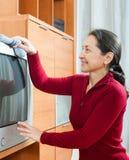 Reife Frau, die Fernsehen am Wohnzimmer abwischt Lizenzfreies Stockfoto
