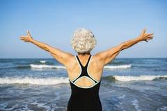 Reife Frau, die frei am Strand glaubt stockbild
