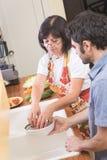 Reife Frau, die Gemüse in der Küche mit Sohn vorbereitet Lizenzfreie Stockfotografie
