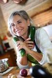 Reife Frau, die Gemüse für das Kochen hält Lizenzfreie Stockfotografie