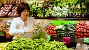 Reife Frau, die grüne Bohnen am Markt kauft stock footage