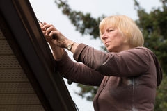Reife Frau, die heraus Dachgossen säubert Stockfotografie