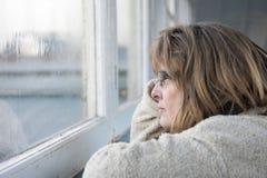 Reife Frau, die heraus das Fenster an einem regnerischen Tag schaut Stockbilder