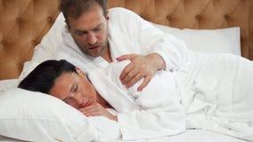 Reife Frau, die, ihre versuchende Unterhaltung des Ehemanns mit ihr im Bett dissapointed schaut stock footage
