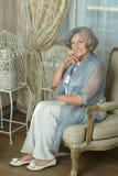 Reife Frau, die im Weinlesesofa sitzt Stockbilder