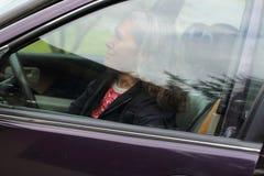 Reife Frau, die innerhalb ihres Autos lächelt Lizenzfreie Stockbilder