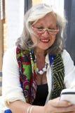 Reife Frau, die intelligentes Telefon unsing ist Lizenzfreie Stockfotografie