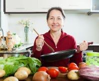 Reife Frau, die mit Bratpfanne kocht Stockfotos