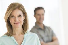 Reife Frau, die mit dem Mann steht im Hintergrund lächelt Stockbild