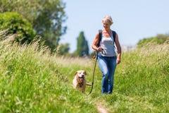 Reife Frau, die mit Hund in der Landschaft wandert Lizenzfreies Stockfoto